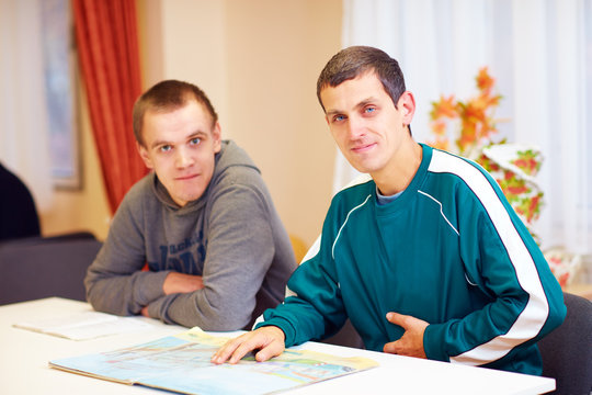 cheerful adult men with disability sitting at the desk in rehabilitation center