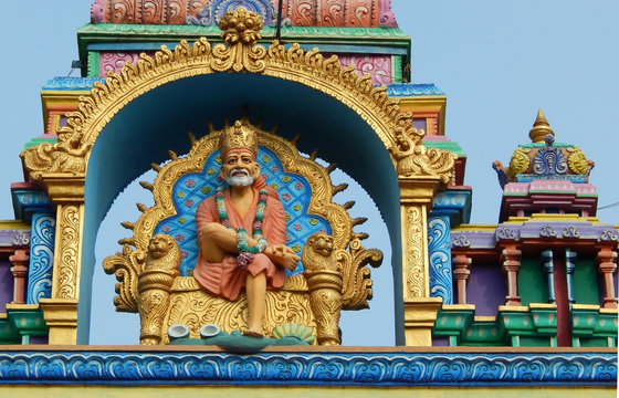 Idol of shirdi Sai Baba in sitting posture on the arch of temple