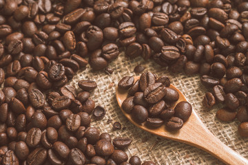 coffee beans on sackcloth and on a wooden spoon, vintage tone