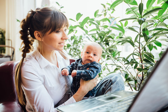 Beautiful young mother working with laptop computer and breastfeeding, holding and nursing her newborn baby at cafe. Mom - business woman feeding newborn.
