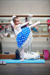 Child girl practicing in a ballet school with wooden floors on the background of mirrors. Little girl ballerina posing at ballet barre in a dance class. Shallow depth of field. Selective focus.