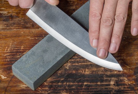 Knife sharpening. Hands holding knife and whetstone on  the old wooden cutting board.