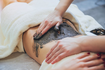 Beautiful woman in spa salon getting mud body massage Wall mural