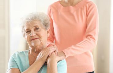 Young girl hugging old woman, closeup