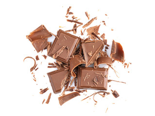 Fototapete - Broken chocolate pieces and shavings on white background