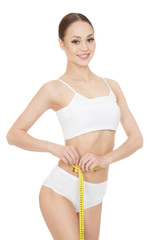 Healthy dieting. Studio portrait of a young cheerful female posing with a meter looking to the camera smiling joyfully on white background.