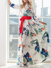 An attractive tall slender blonde woman in a beautiful bright dress with a floral print stands next to a full-length window