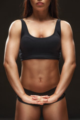 Focused on result. Cropped studio shot of a fit female athlete stretching her hands on black background.