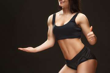 Getting better. Cropped studio shot of a beautiful muscular woman holding the copyspace showing thumbs up on black background.