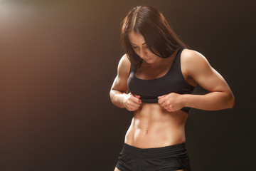 Perfect abs. Horizontal shot of a gorgeous female athlete posing at the studio looking at her abs copyspace on the side on black background.