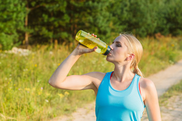 Young woman drinks water outside in the natural environment