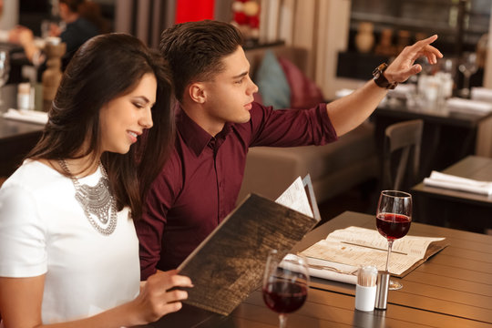 Young loving couple choosing from restaurant menu