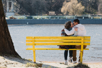 Happy couple in love hugging and sharing emotions, holding hands on a bench by the river