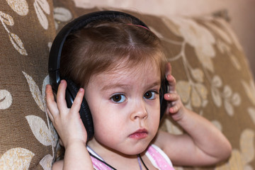 The child listens to music with headphones