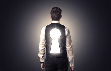 Man standing with black keyhole on his back