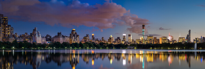 Panoramic view of the Central Park Reservoir and Midtown skyscrapers illuminated at twilight in Summer. Manhattan, New York City