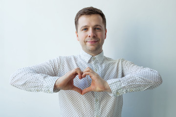 young caucasian man making out of hands heart. Doing charity work, take care of the health, or being in love