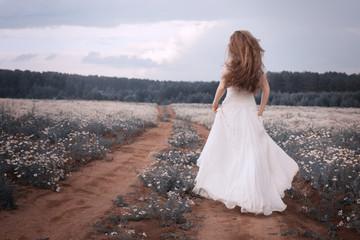 Runaway bride. Woman in a wedding dress runs on flower field. Toned portrait.