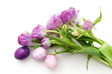 Easter eggs and tulips on white background. Flat lay. Top view
