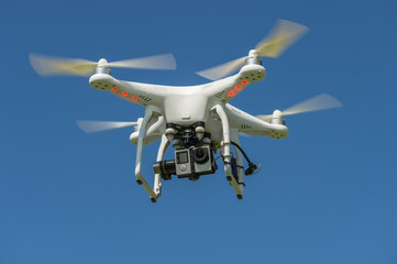 quadrocopter with the camera in flight against a blue sky