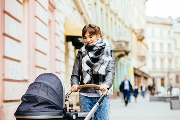 Young beautiful mother walking with baby carriage in europen city center.