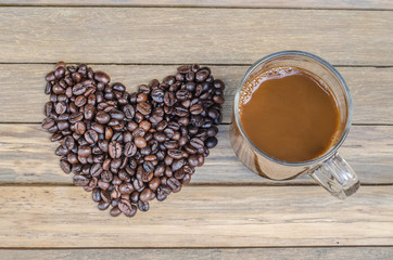 Cup with coffee and heart of coffee beanes on wood backround