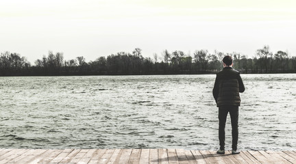 teenager standing on the edge of a pier near the water