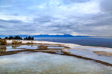 Pamukkale travertines with snowy mountains background