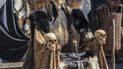 Throne of furs and skulls with a Viking sword. Chair with animal skins