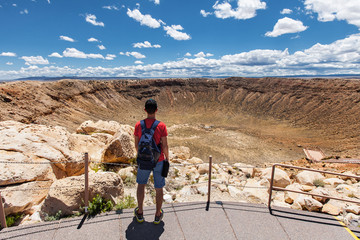 Travel in Meteor Crater, man hiker with backpack enjoying view, Winslow, Arizona, USA