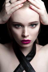 Portrait of beautiful girl model with pink lips and blue eyes with leather belt on her neck, fresh clean highlighted skin. Fashion retouched close up shot.