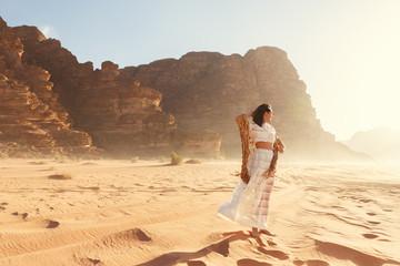 Stylish girl in white dress in Wadi Rum desert in Jordan