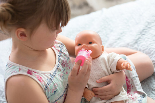 Kid girl playing with doll, feeding doll bottle