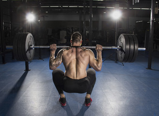 Attractive muscular bodybuilder doing heavy squat exercise in mo