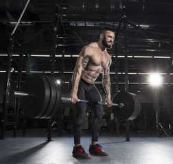 Attractive muscular athlete doing heavy deadlift exercise in mod