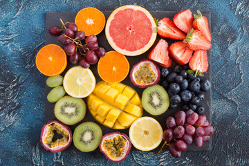 Raw fruits platter: oranges, lemons, kiwis, grapefruits, strawberries, grapes, blueberries, passion fruit, mango on the black slate on the dark blue background, top view