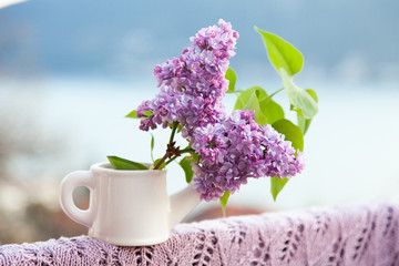 Fotomurales - Beautiful spring lilac flowers with green leaves are in white vase stands on knitted violet tablecloth on balcony with view of sea and mountains.