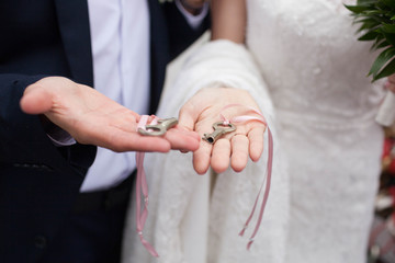 The keys in the hands of the bride and groom. Wedding tradition.
