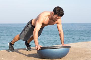 Athletischer Mann macht Liegestütze auf Plattform am Meer