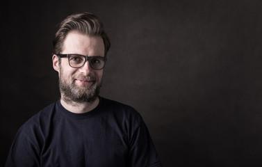 Dark moody portrait of happy caucasian man in glasses