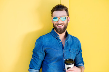Portrait of a handsome man in blue t-shirt standing with coffee to go on the yellow background