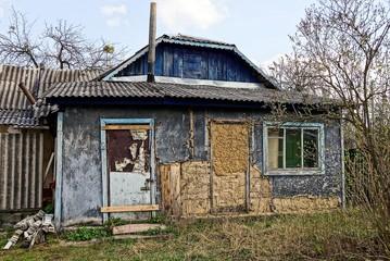 Фасад старого сельского домика во дворе с зелёной траве