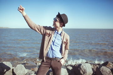 Young fashion metrosesual hipster man making selfie at the sea. Mobile photo concept.