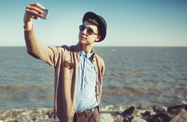Young fashion metrosesual hipster man making selfie at the sea. Mobile photo concept. Vintage photo