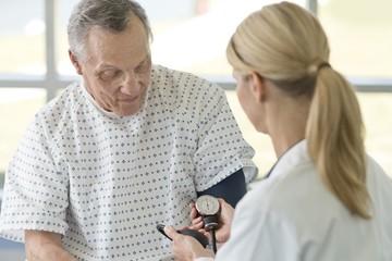 Female doctor taking senior man's blood pressure
