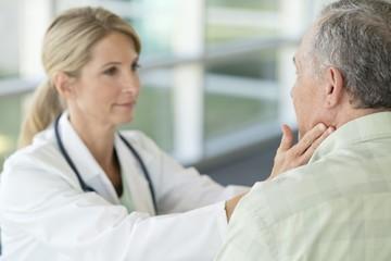 Female doctor touching senior man's neck