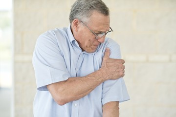 Senior man holding his left arm in pain