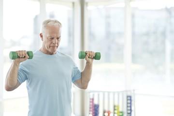 Senior man using weights