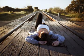 Joven tumbada en las vías del tren mirando al cielo.