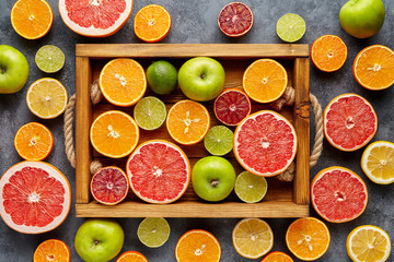 Different citrus fruit on a wooden box and grey concrete table. Fruit food background. Antioxidant, detox, dieting, clean eating, vegetarian, vegan, fitness or healthy lifestyle concept. Flat lay.